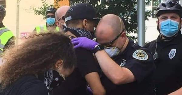 Thousands Encouraged by Photo of Police Officer and Protester Praying Together